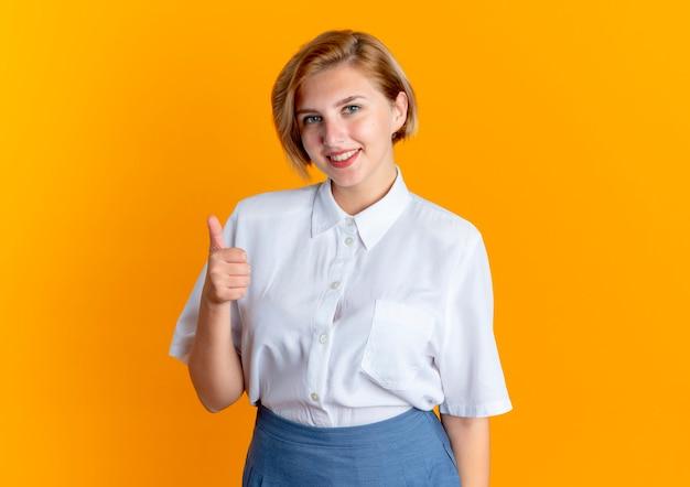Jong lachend blond russisch meisje duimen omhoog kijken camera geïsoleerd op een oranje achtergrond met kopie ruimte