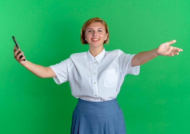 Jong lachend blond russisch meisje houdt telefoon met open armen geïsoleerd op groene achtergrond met kopie ruimte