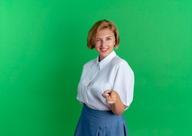 Jong lachend blond russisch meisje knippert oog en wijst op camera geïsoleerd op groene achtergrond met kopie ruimte