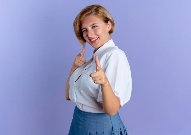 Jong lachend blond russisch meisje staat zijwaarts knippert oog wijzend op camera geïsoleerd op paarse achtergrond met kopie ruimte