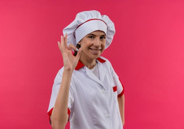 Jong lachend kaukasisch kokmeisje in chef-kok uniforme gebaren ok handteken geïsoleerd op roze achtergrond met kopie ruimte