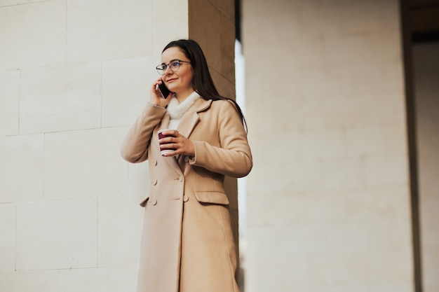 Jong lachend meisje in beige jas en bril praten op de smartphone en koffie drinken in de stad in de buurt van gebouw.