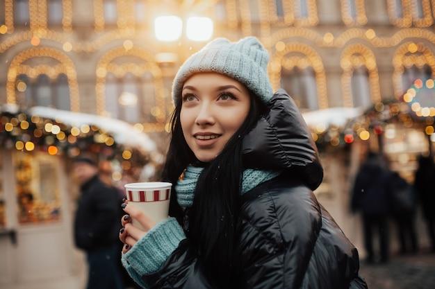 Jong lachend meisje in de winter op kerstmarkt