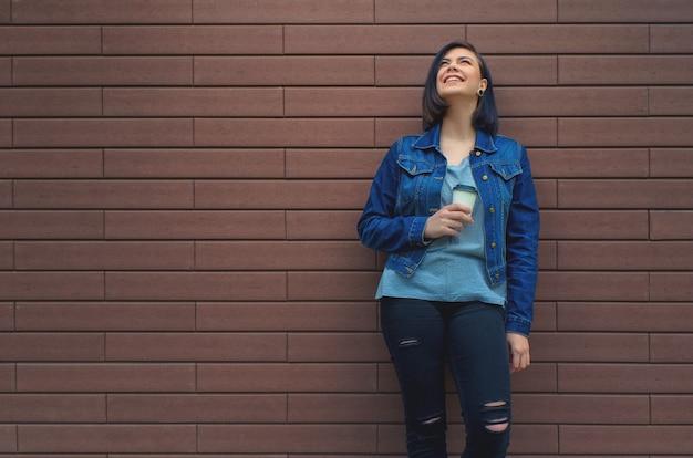 Jong lachend meisje in jeans jasje in de buurt van een bruine bakstenen muur met een kopje koffie in haar hand opzoeken.