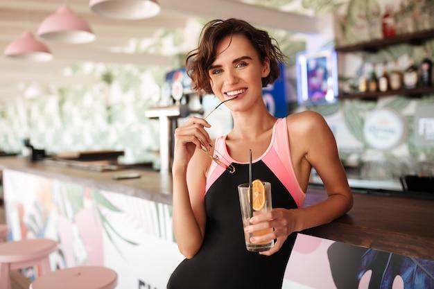 Jong lachend meisje in trendy zwembroek leunend op strand toog met zonnebril en cocktail in handen