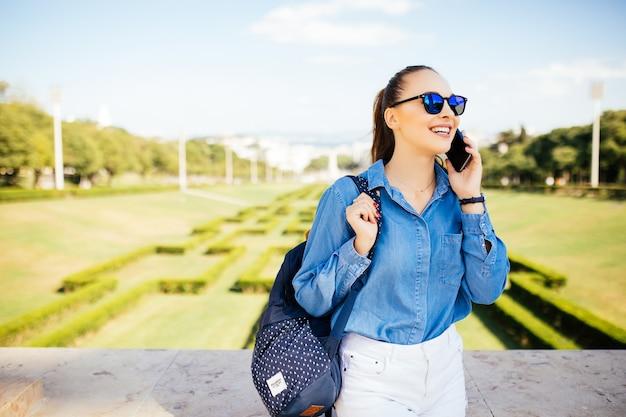 Jong lachend meisje in zonnebril permanent in een park terwijl wegkijken en praten aan de telefoon