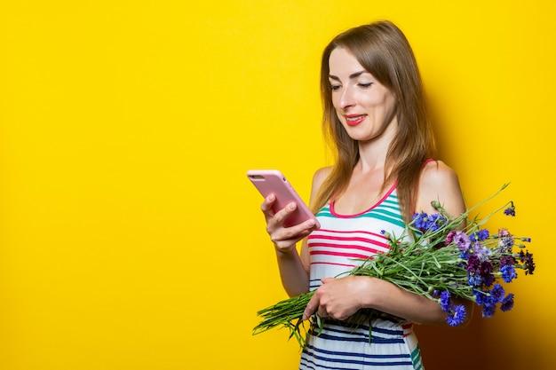 Jong lachend meisje kijkt naar de telefoon, houdt een boeket van wilde bloemen