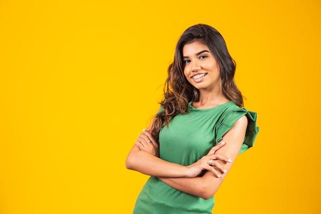Jong lachend meisje met armen gekruist op gele achtergrond.