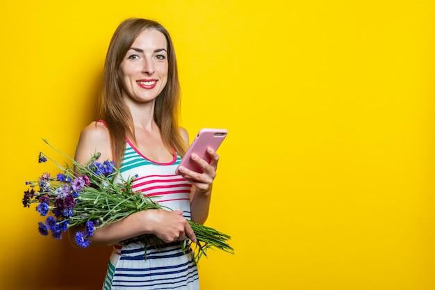 Jong lachend meisje met een telefoon en een boeket wilde bloemen
