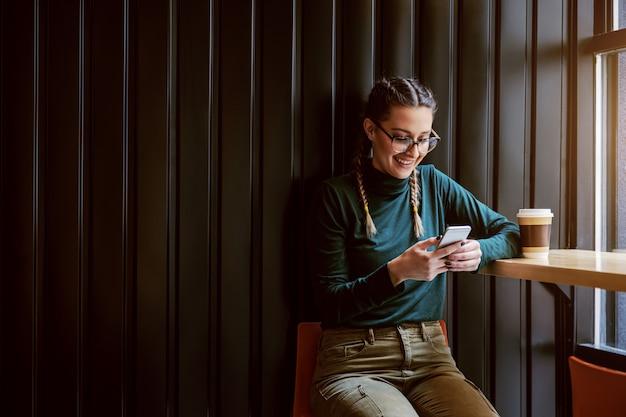 Jong lachend meisje met vlechten zitten in coffeeshop, een pauze nemen en slimme telefoon gebruiken om op sociale media te hangen.