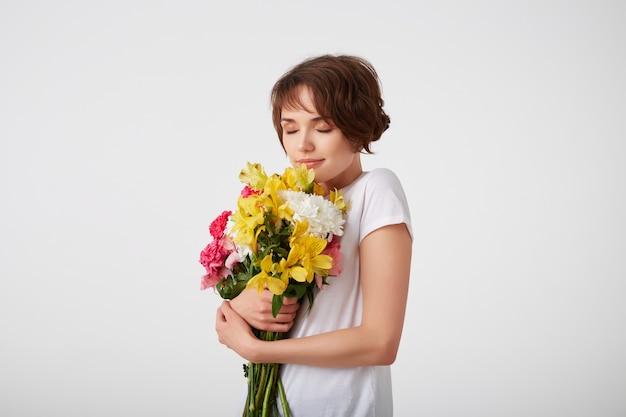 Jong lachend mooi kortharig meisje in wit leeg t-shirt, met een boeket van kleurrijke bloemen, genietend van de geur, staande op een witte achtergrond met gesloten ogen.