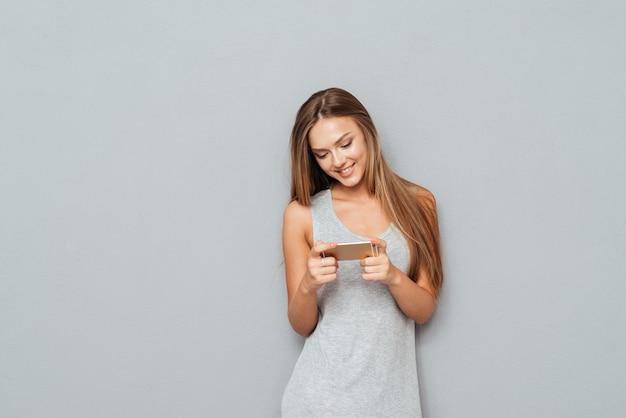 Jong lachend mooi meisje bericht aan het typen op smartphone geïsoleerd op een grijze achtergrond