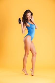 Jong lachend mooi meisje in zwembroek poseren en houden glazen fles geïsoleerd op de oranje muur