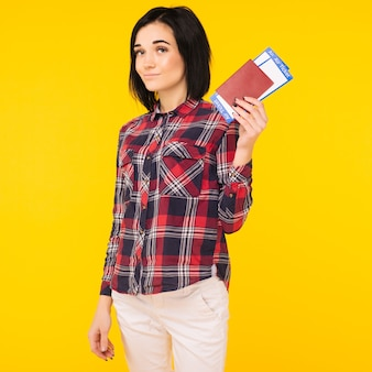 Jong lachend opgewonden vrouw student paspoort instapkaart ticket geïsoleerd op gele achtergrond te houden. opleiding aan een hogeschool in het buitenland. vliegreizen vlucht - afbeelding