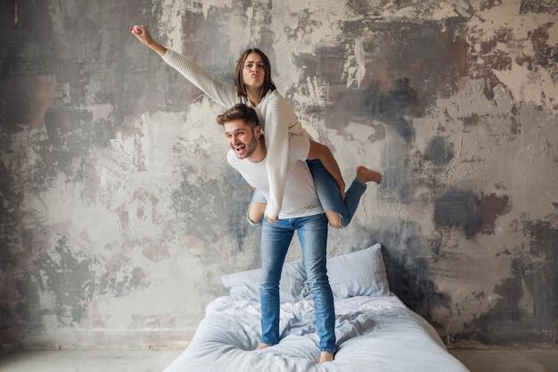 Jong lachend paar spelen op bed thuis in casual outfit, man en vrouw samen plezier hebben, gekke positieve emotie, gelukkig, hand omhoog houden