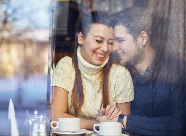 Jong lachend paar, zittend in het café, knuffelen en koffie drinken.