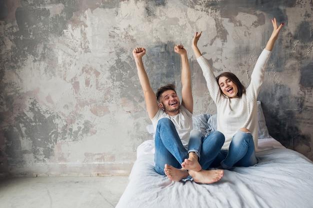 Jong lachend paar zittend op bed thuis in casual outfit, man en vrouw samen plezier hebben, gekke positieve emotie, gelukkig, hand in hand