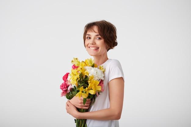 Jong lachend schattig kortharig meisje in wit leeg t-shirt, met een boeket van kleurrijke bloemen, erg blij met zo'n geschenk van haar vriend, bijt op zijn lip en glimlacht over witte muur.