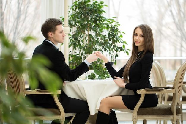 Jong lachend stel romantiserend aan een tafel in een restaurant