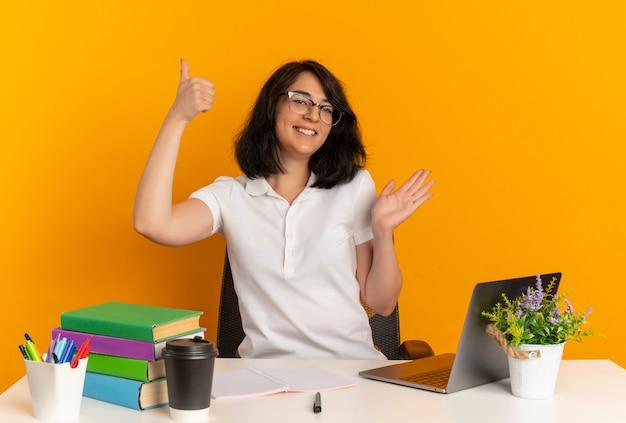 Jong lachend vrij kaukasisch schoolmeisje met bril zit aan bureau met school tools duimen omhoog en wijst met de hand aan de zijkant geïsoleerd op oranje ruimte met kopie ruimte