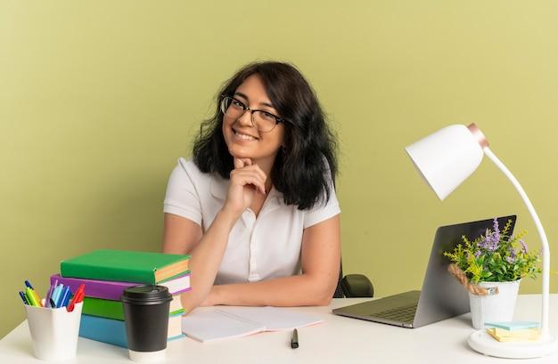 Jong lachend vrij kaukasisch schoolmeisje met bril zit aan bureau met schoolhulpmiddelen zet hand op kin geïsoleerd op groene ruimte met kopie ruimte