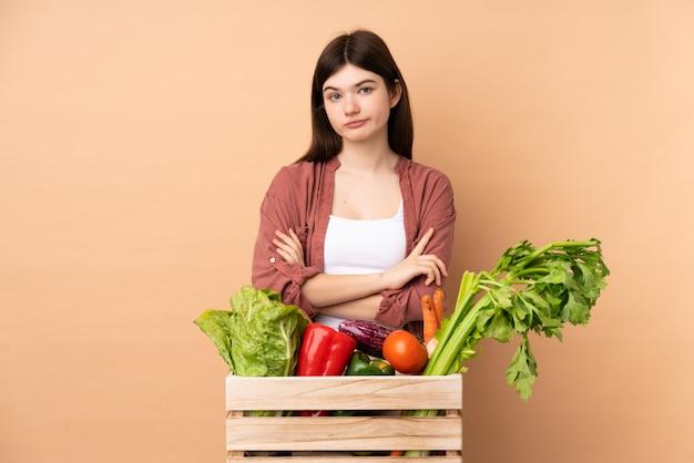 Jong landbouwersmeisje met vers geplukte groenten in een doos die verstoord voelen