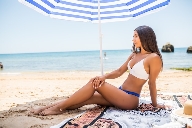 Jong latijns-meisje in bikini die onder kleurenparaplu op het strand in zonnige hete dag liggen.