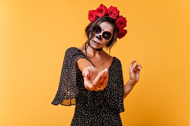 Jong latijns model roept met de hand om zich bij haar aan te sluiten. portret van donkerharige vrouw in beeld van skelet op geïsoleerde muur
