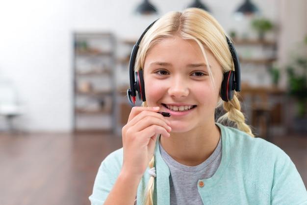 Jong leerlingsmeisje dat op hoofdtelefoons spreekt