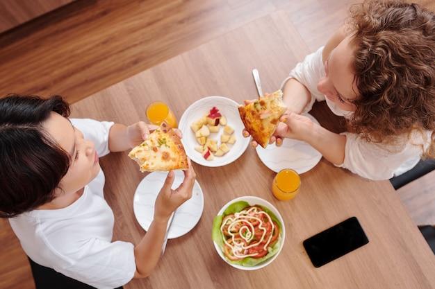 Jong lesbisch koppel dat pizzapunten eet met zelfgemaakte salade tijdens het eten thuis, uitzicht vanaf de top