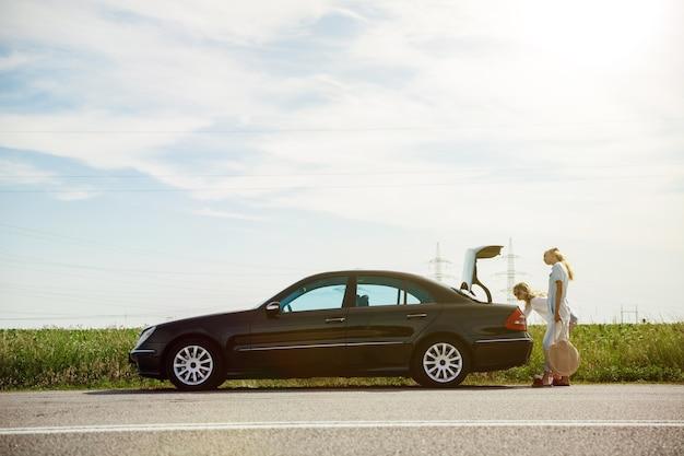 Jong lesbisch koppel gaat op vakantie reis op de auto in zonnige dag