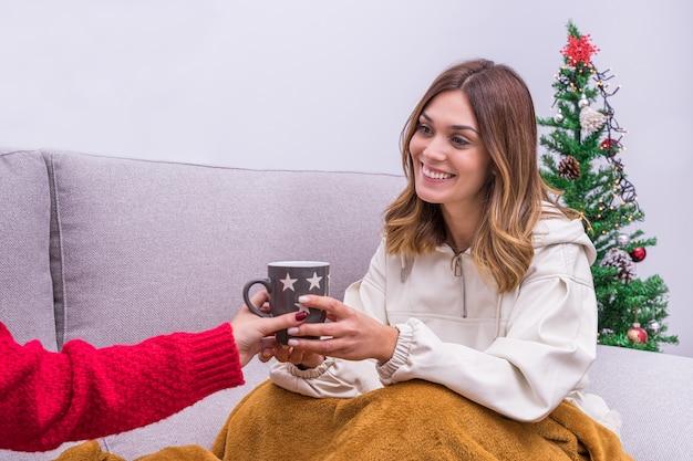 Jong lesbisch koppel koffie drinken en plezier maken bij de kerstboom.