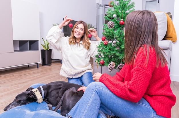 Jong lesbisch koppel met plezier met het versieren van de kerstboom met hun hond, prettige kerstdagen en gelukkig nieuwjaar concept. fijne vakantie. ruimte voor tekst