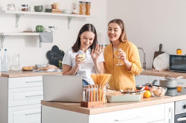 Jong lesbisch koppel wijn drinken terwijl videochatten met vrienden in de keuken