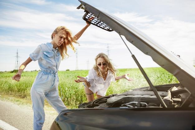 Jong lesbisch paar gaat op vakantie reis op de auto in zonnige dag