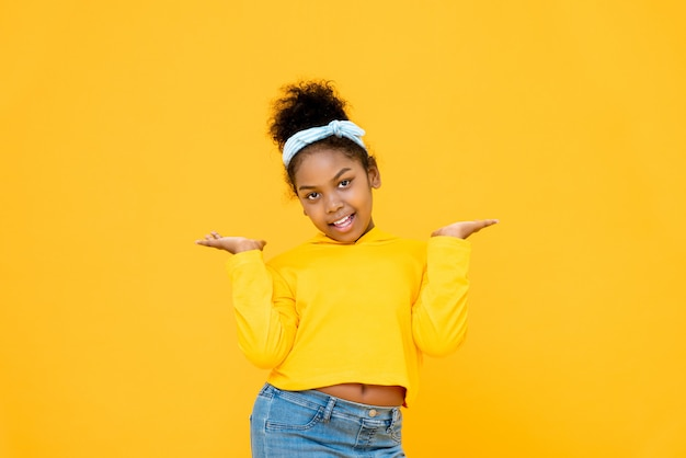 Jong leuk afrikaans amerikaans gemengd rasmeisje die en open die palmengebaar glimlachen doen op kleurrijke gele muur wordt geïsoleerd