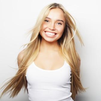 Jong leuk glimlachend blond meisje op witte achtergrond