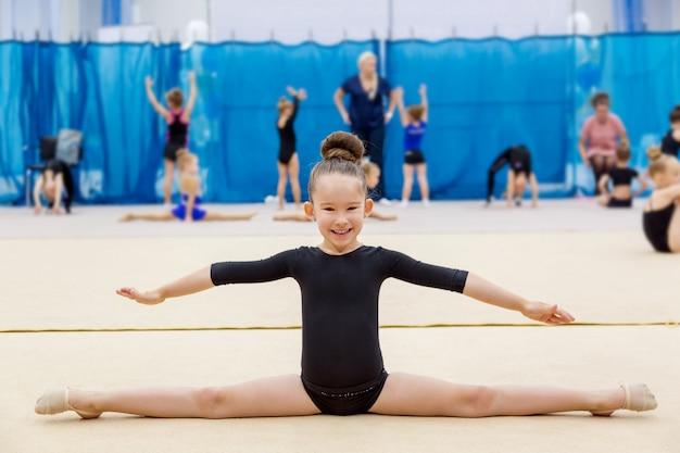Jong leuk glimlachend meisje dat spleet in gymnastiek- zaal doet.