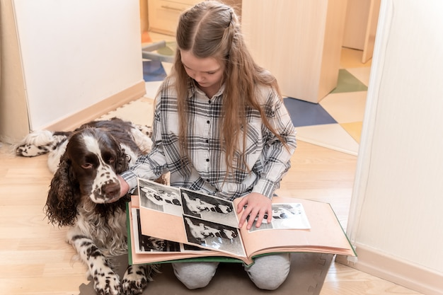 Jong leuk meisje dat fotoalbum thuis met haar hond op vloer kijkt.