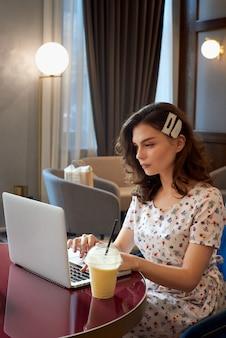 Jong leuk meisje in kleding die aan laptop in koffiewinkel werkt