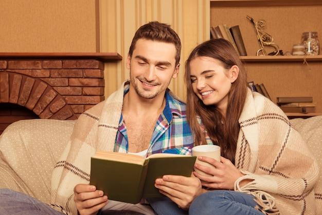 Jong leuk paar dat samen onder de plaid leest