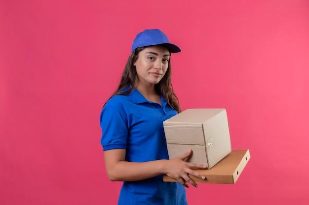 Jong levering meisje in blauw uniform en pet met kartonnen dozen glimlachend zelfverzekerd positief en gelukkig staande over roze achtergrond