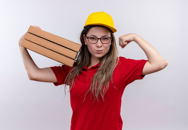 Jong levering meisje in rood poloshirt en gele pet met stapel pizzadozen die zich voordeed als een winnaar met biceps glimlachend zelfverzekerd