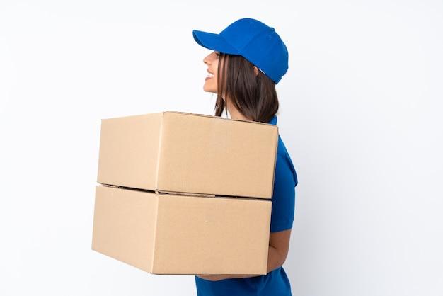 Jong leverings donkerbruin meisje over geïsoleerde witte achtergrond in zijpositie