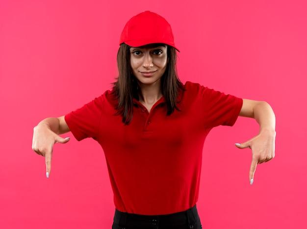 Jong leveringsmeisje dat een rood poloshirt en een pet draagt die met wijsvingers naar beneden gericht glimlachend zelfverzekerd over roze muur wijst