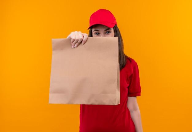 Jong leveringsmeisje dat rode t-shirt in rode glb draagt die een pakket op gele achtergrond houdt