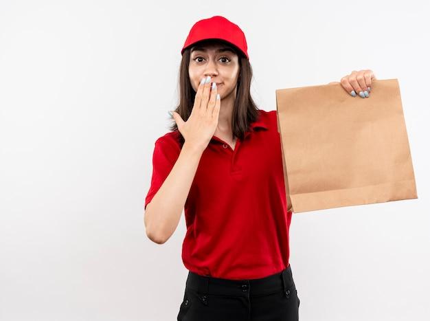 Jong leveringsmeisje die rood uniform en glb dragen die document pakket houden die camera bekijken verbaasd coneting mond met hand die zich over witte achtergrond bevindt
