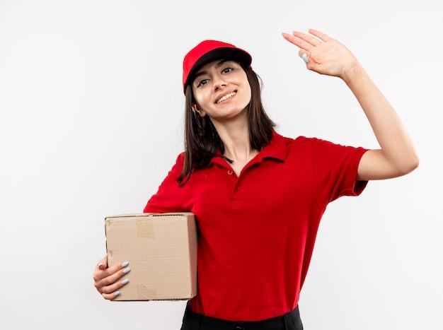 Jong leveringsmeisje die rood uniform en glb dragen die kartondoos houden die met gelukkig gezicht glimlachen die ok teken tonen dat zich over witte muur bevindt