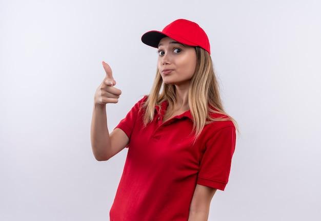 Jong leveringsmeisje die rood uniform en glb dragen die pistoolgebaar tonen dat op witte muur wordt geïsoleerd