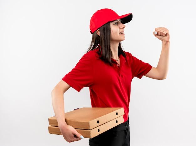Jong leveringsmeisje die rood uniform en pet dragen die pizzadozen vasthouden die vuist balanceren die zelfverzekerd over witte muur kijken